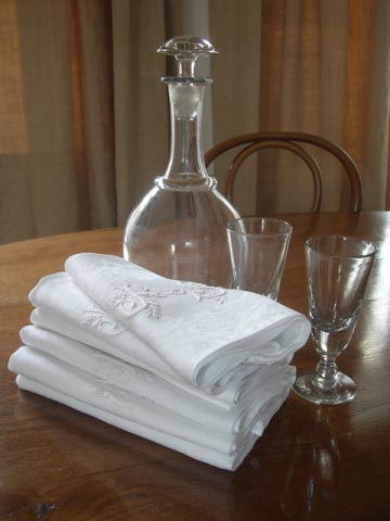 Early 20th century damask napkins and late 19th century Normandy cider carafe with bistrot glasses.